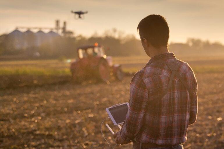Farmer Controlling Drone in Field