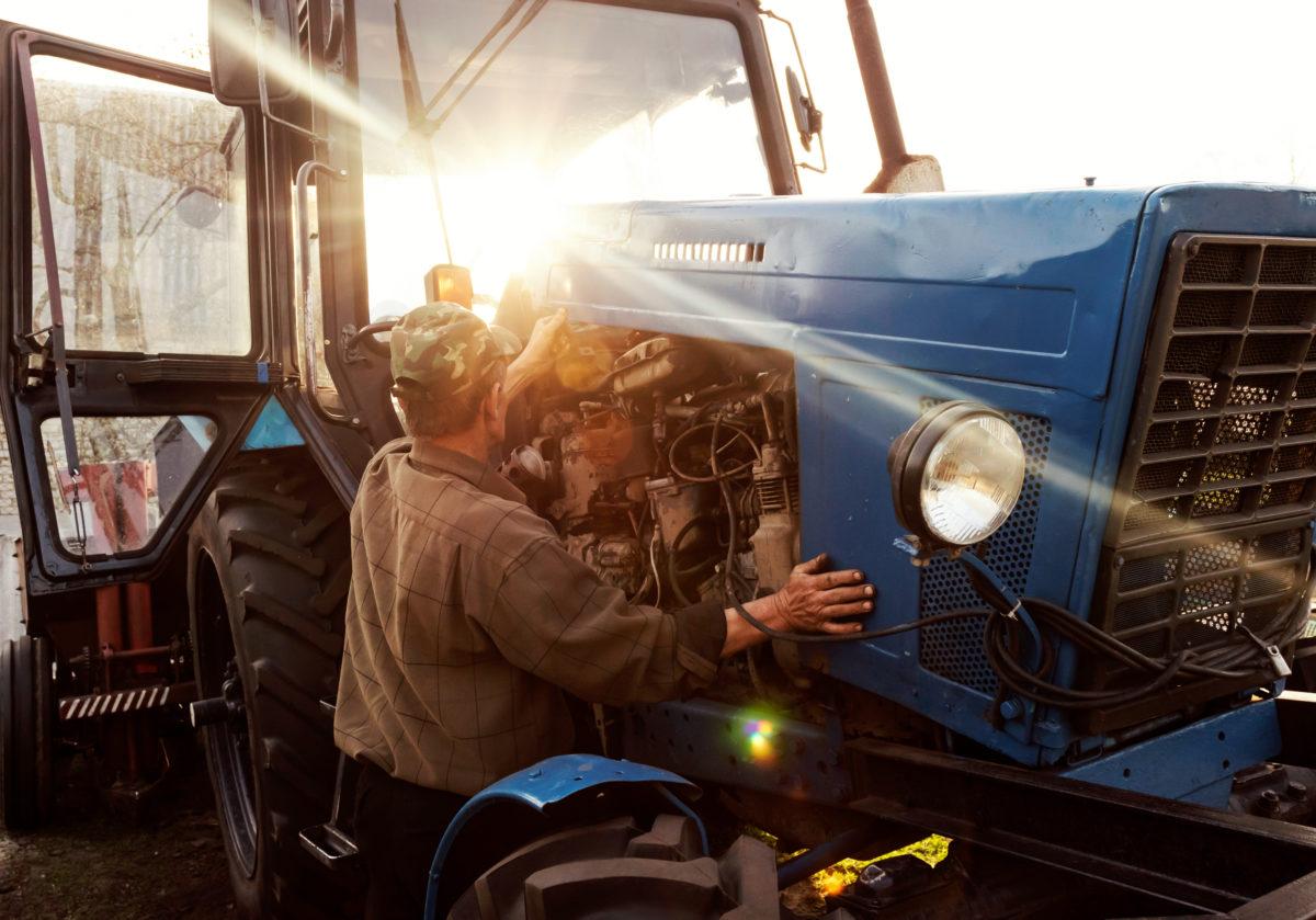 Farmer Repairing Tractor